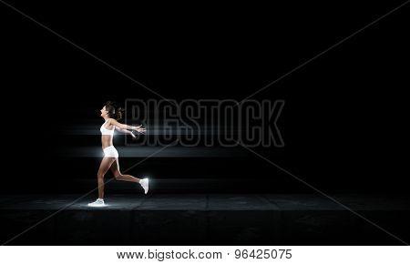 Running woman in sport wear on black background