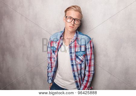 Casual young man holding both hands in pockets while leaning on a wall.