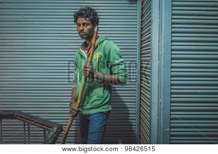 VARANASI, INDIA - 20 FEBRUARY 2015: Young Indian man holds broom stick and stands next to closed stores. Post-processed with grain, texture and colour effect.