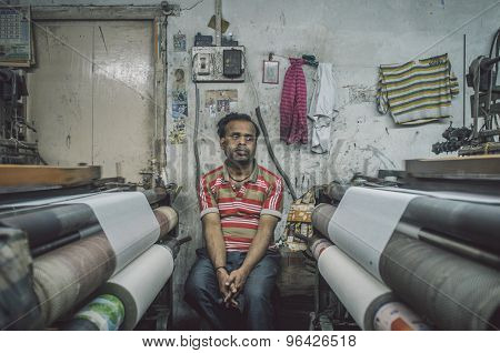 VARANASI, INDIA - 21 FEBRUARY 2015: Worker sits on chair next to textile machine in small factory and looks away. Post-processed with grain, texture and colour effect.