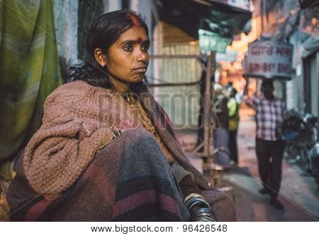 VARANASI, INDIA - 25 FEBRUARY 2015: Indian homeless woman sitting in street. Post-processed with grain, texture and colour effect.