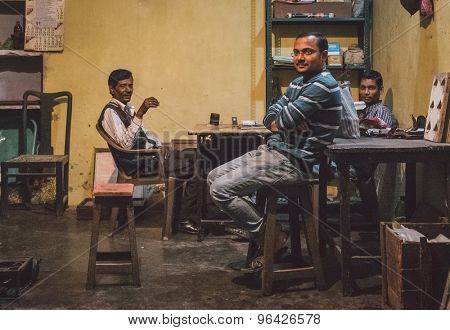 VARANASI, INDIA - 19 FEBRUARY 2015: Three Indian men sit in store after long working day. Post-processed with grain, texture and colour effect.
