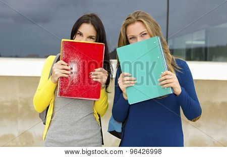 Beautiful and happy teenagers students covering the faces with school books