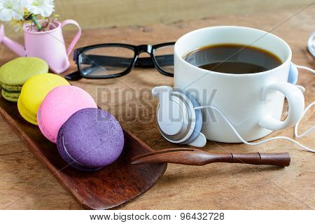Colorful Macaroons And A Cup Of Coffee With Cellphone On Wooden Table