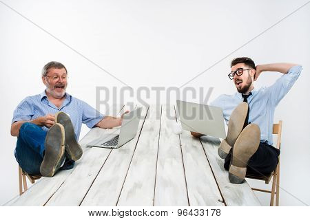 The two businessmen with legs over table working on laptops