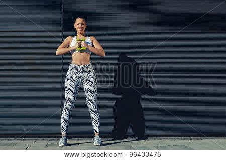 Young woman in sporty clothing training bicep curls outdoors with copy space background