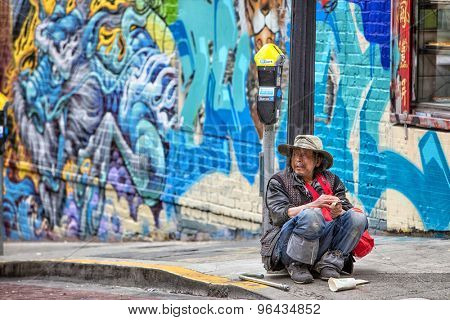 San Francisco, USA - June 22nd, 2015: Man who appears to be experiencing hard times sitting on street ground in Chinatown in San Francisco