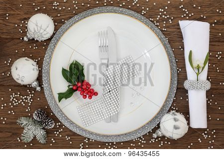 Christmas dinner place setting with plate, napkin, cutlery, bauble decorations with holly and mistletoe over oak table background.