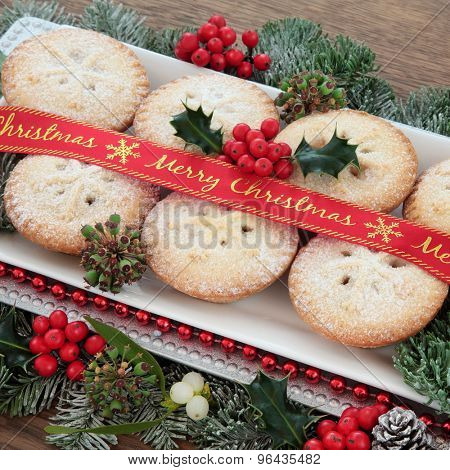 Mince pie cakes with merry christmas ribbon, holly, mistletoe and winter greenery over white background.