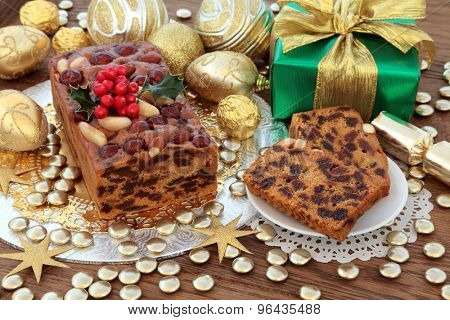 Genoa cake with gold christmas bauble decorations, holly and gift box over oak background.
