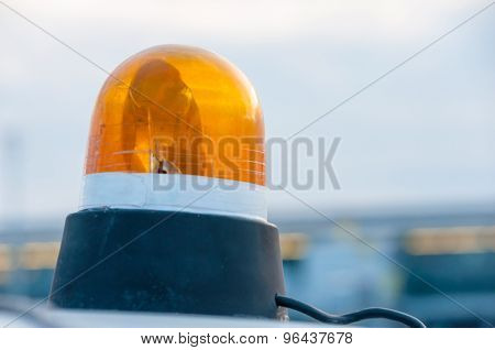 Orange flashing and revolving light on top of a support services vehicle
