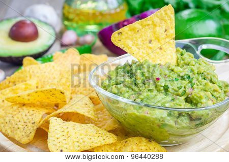 Bowl With Chunky Guacamole Served With Nachos And Ingredients On Backgroung