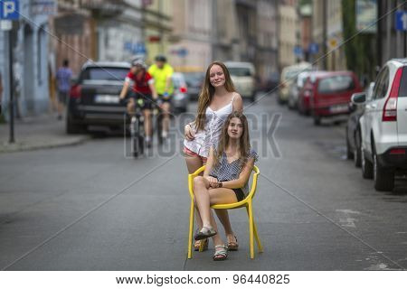 Two young best girlfriends in the old European town, conceptual photo about the vacation.