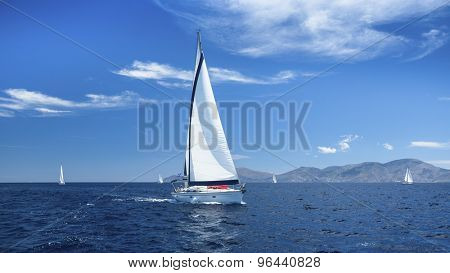 Sailing boats with white sails in the Sea. Luxury ship yachts.