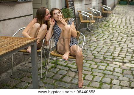 Two young best girlfriends sitting at the table of outdoors cafe and whispering.