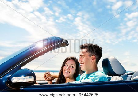 Happy Couple Driving Convertible Along Seaside.