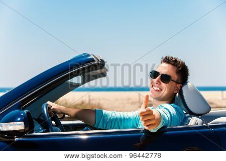 Young Man In Convertible Doing Thumbs Up.