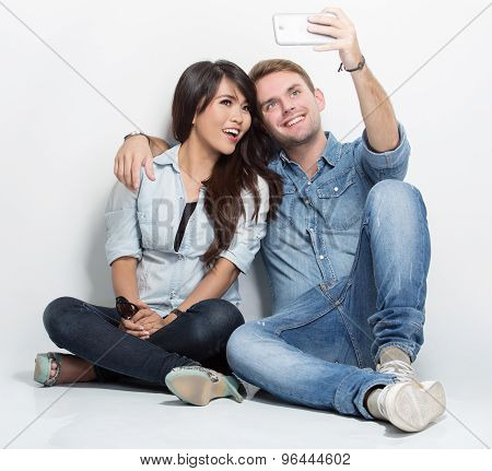 Mixed Couple Sitting On The Floor Taking Self Camera Together