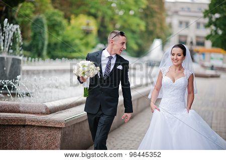 Newlyweds Walking Near Fountain