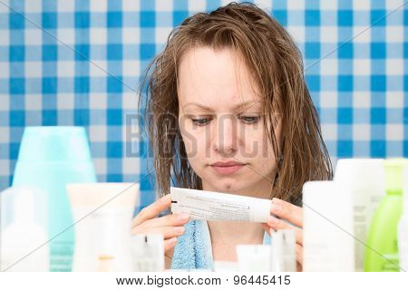 Girl Is Reading Inscription On Cosmetic Product
