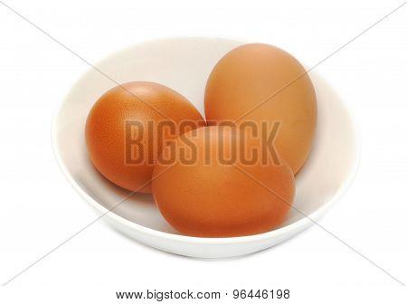 Three brown chicken eggs on a white saucer
