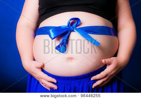 Hands women on pregnant belly