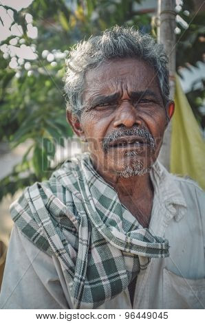 HAMPI, INDIA - 31 JANUARY 2015: Indian elderly man with checked scarf. Post-processed with grain, texture and colour effect.