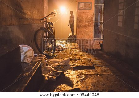 VARANASI, INDIA - 19 FEBRUARY 2015: Adult man in street with parked bicycle and leftover trash from street vendor. Post-processed with grain, texture and colour effect.