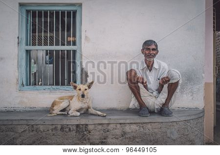 GODWAR REGION, INDIA - 15 FEBRUARY 2015: Elderly Indian man and dog sit oudoors in front of home. Post-processed with grain, texture and colour effect.