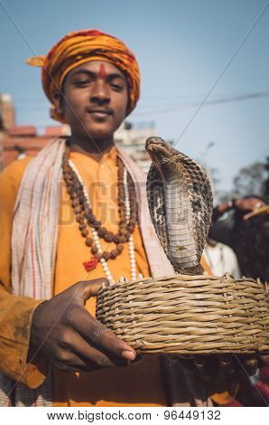 VARANASI, INDIA - 23 FEBRUARY 2015: Indian boy dressed up in religious clothes holds cobra in basket. Post-processed with grain, texture and colour effect.