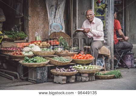 MUMBAI, INDIA - 17 JANUARY 2015: Elderly Indian man writes in book and waits for customer next to grocery shop in market street. Post-processed with grain, texture and colour effect.