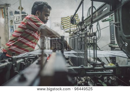 VARANASI, INDIA - 21 FEBRUARY 2015: Worker repairs textile machine in small factory. Post-processed with grain, texture and colour effect.