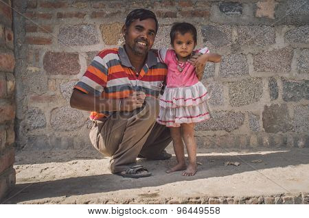 GODWAR REGION, INDIA - 15 FEBRUARY 2015: Happy father holds baby girl under shoulder in front of home. Child wears white and pink dress. Post-processed with grain, texture and colour effect.