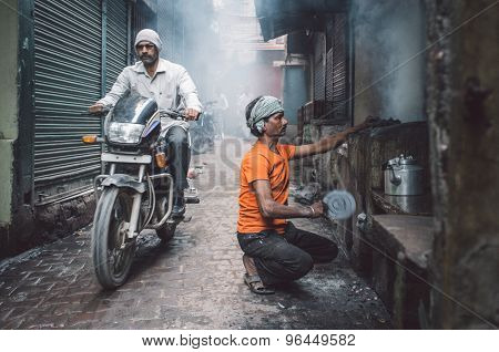 VARANASI, INDIA - 20 FEBRUARY 2015: Street vendor makes fire for milky tea in coal oven while motorcyclist passes by. Post-processed with grain, texture and colour effect.