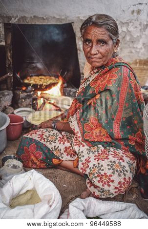KAMALAPURAM, INDIA - 02 FABRUARY 2015: Elderly Indian woman in traditional clothes fries vegatables. Post-processed with grain, texture and colour effect.