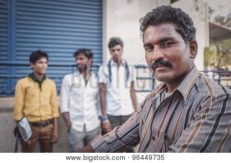 KAMALAPURAM, INDIA - 02 FABRUARY 2015: Indian man on motorbike next to three young men on market close to Hampi. Post-processed with grain, texture and colour effect.