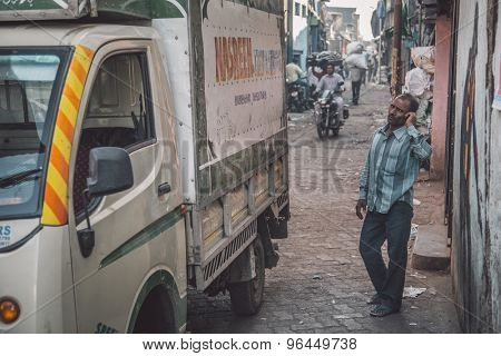 MUMBAI, INDIA - 12 JANUARY 2015: Indian man stands next to truck in Dharavi slum and talks on cellphone. Post-processed with grain, texture and colour effect.