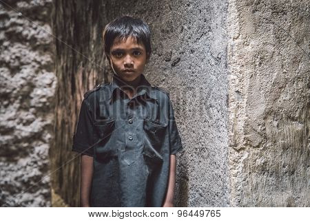 MUMBAI, INDIA - 12 JANUARY 2015: Young Indian boy from Dharavi slum stands in empty narrow street. Post-processed with grain, texture and colour effect.