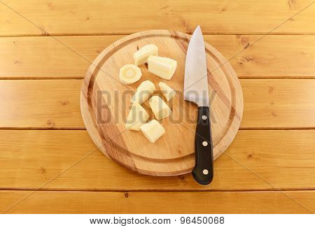 Chopped Parsnip With A Kitchen Knife On A Wooden Board