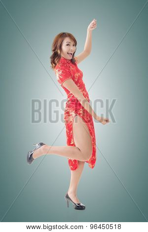 Attractive Chinese woman dress traditional cheongsam and hold something, full length portrait.
