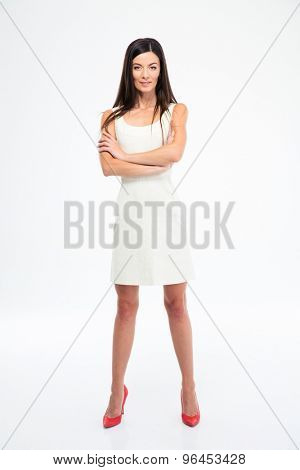 Full length portrait of a beautiful smiling woman in dress standing with arms folded isolated on white background. Looking at camera