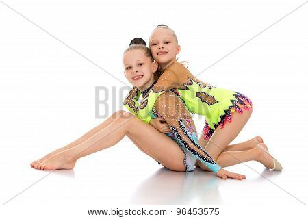 Little gymnasts sitting on the floor