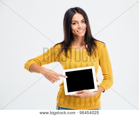 Portrait of a happy attractive woman pointing finger on blank tablet computer screen isolated on a white background. Looking at camera