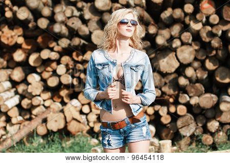 Portrait Of A Beautiful Woman In Sunglasses In Denim Shorts And Jeans Jacket On The Sawmill.