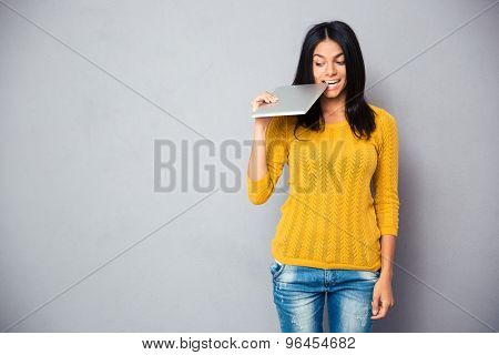 Casual woman biting tablet computer over gray background