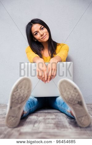 Young beautiful woman sitting on the floor with laptop on gray background