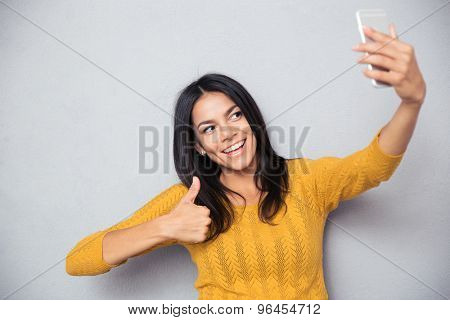 Happy cute woman making selfie photo on smartphone and showing thumb up over gray background