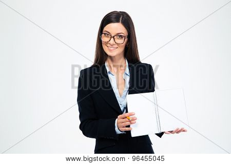 Smiling businesswoman in glasses showing blank notebook isolated on a white background. Looking at camera