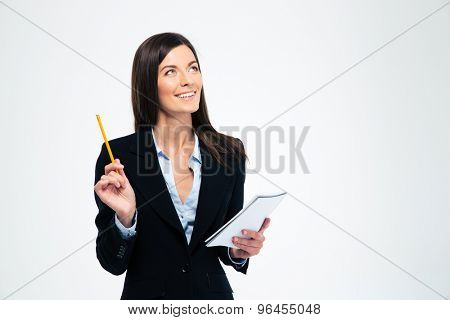 Happy businesswoman holding pencil with notebook and looking up isolated on a white background