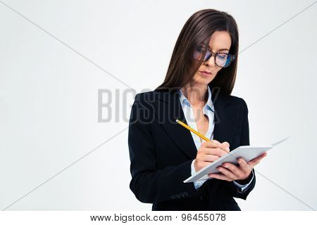 Beautiful businesswoman in glasses writing notes in notebook isolated on a white background